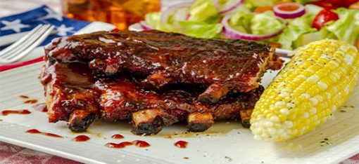 stack of ribs with bbq sauce and corn